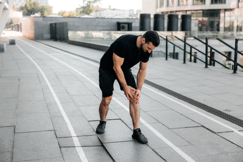 male-hands-holding-aching-knee-strong-man-feeling-pain-his-foot-during-jogging-outdoors-close-up-male-runner-black-sneakers-standing-feeling-cramps-his-left-leg-cut-view