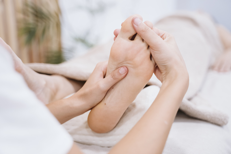 young caucasian physiotherapist Woman giving a feet massage to female patient in clinic. Physiotherapy and body care concept