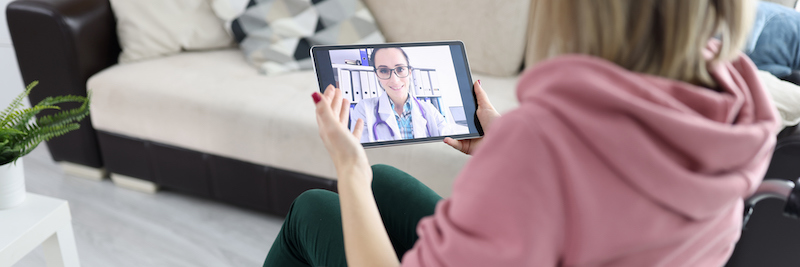 Woman in wheelchair holding tablet with picture closeup