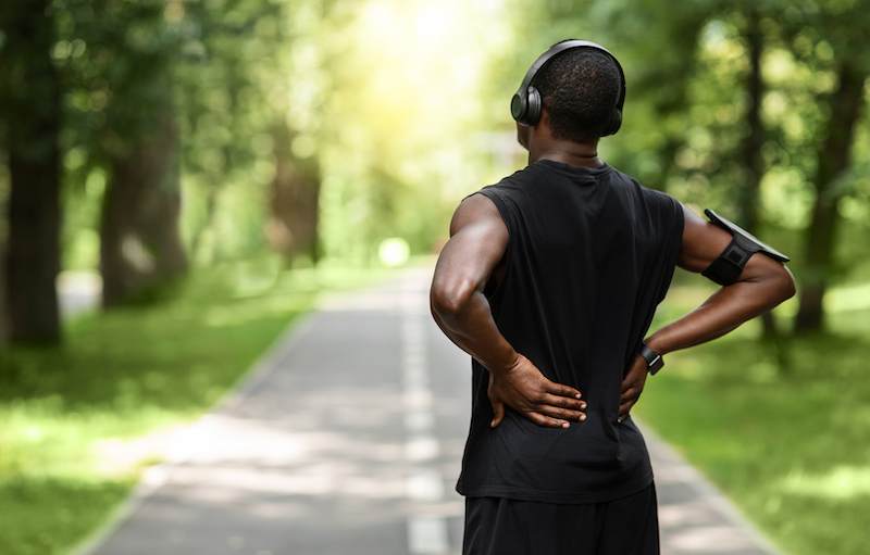 African guy sportsman rubbing his back, exercising at park