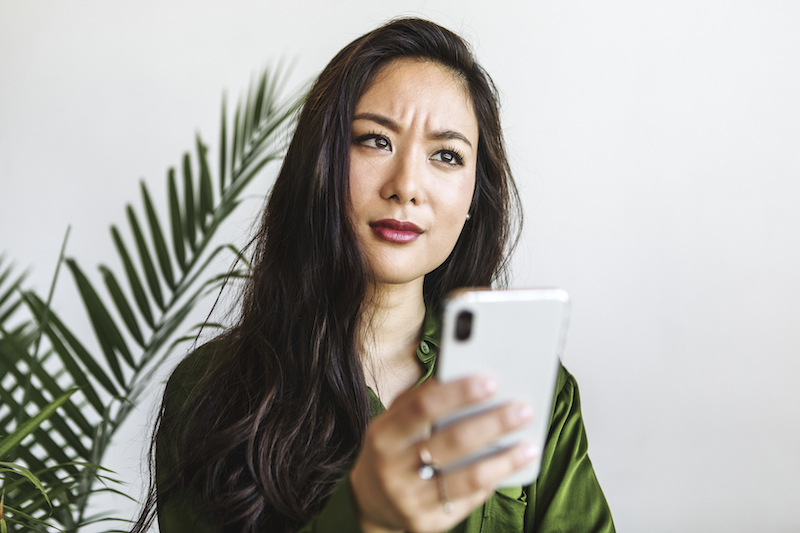 Thoughtful businesswoman using a smartphone