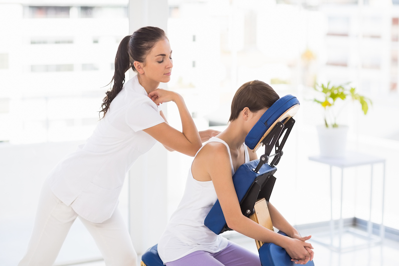 Masseuse giving back massage to woman on chair at spa