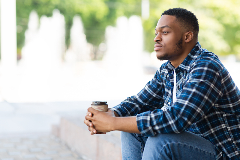 Portrait of pensive african american guy sitting with coffee