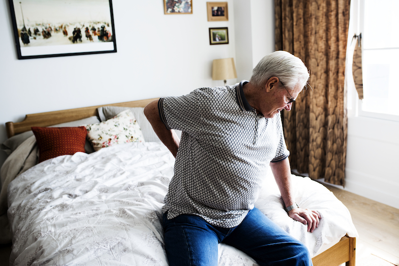 Senior man sitting on the bed in pain